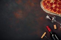 O coração deu forma à pizza com a mussarela, sausagered com uma garrafa do vinho e dos wineglas Cartão do dia de Valentim no back fotografia de stock royalty free