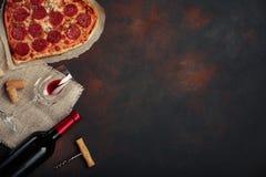 O coração deu forma à pizza com mussarela, sausagered com uma garrafa do vinho e dos wineglas no fundo oxidado foto de stock