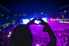 O coração deu forma às mãos no concerto, mulher no festival que ama o artista e a música imagem de stock