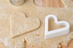 O coração deu forma ao cortador do biscoito na massa crua do biscoito e em uma coração-forma Foto de Stock