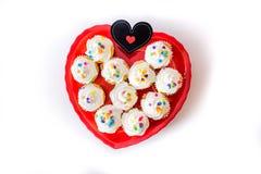 O coração deu forma ao prato vermelho completamente de queques brancos geados e de c preto Fotos de Stock