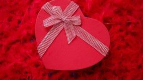 O coração deu forma ao presente encaixotado, colocado no fundo vermelho das penas filme