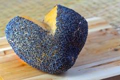O coração deu forma ao rolo de pão com as sementes de papoila na madeira fotografia de stock