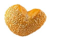 O coração deu forma ao rolo de pão com o sésamo isolado no branco fotografia de stock royalty free