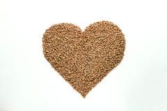 O coração deu forma ao trigo mourisco no fundo branco fotografia de stock