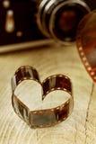 O coração deu forma feito do negativo de filme retro na placa de madeira com bokeh da câmera do vintage Fotografia de Stock