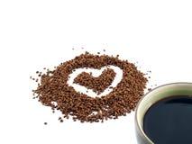 O coração deu forma no pó do café instantâneo e em uma xícara de café imagens de stock