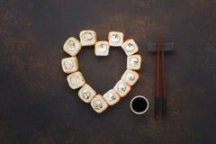 O coração deu forma a rolos de sushi com hashis e molho de soja imagem de stock