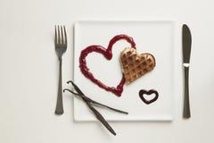 O coração deu forma a waffles, doce de fruta, molho de chocolate, varas da baunilha Fotografia de Stock Royalty Free