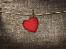O coração do cartão do Valentim deu forma do paperr vermelho velho que pendura em um clo imagem de stock