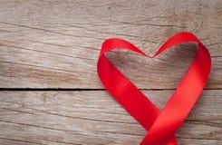 O coração do dia de Valentim deu forma à fita sobre o fundo de madeira da tabela Fotos de Stock