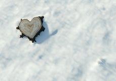 O coração do Valentim deu forma ao tronco na neve, espaço da cópia Fotos de Stock