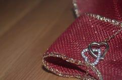 O coração dois limitou junto a colar feito a mão na tabela de madeira - conceito do amor foto de stock