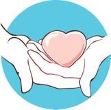 O coração encontra-se nas mãos em um fundo azul Foto de Stock