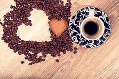 O coração faz feijões de café do whit e café do whit do copo e cookie do querido no fundo de madeira da tabela Foto de Stock