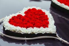 O coração feito de rosas vermelhas e brancas encontra-se na capa preta fotografia de stock