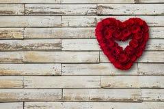 O coração feito do vermelho de madeira das rosas pintou a suspensão de uma parede da madeira Fotografia de Stock Royalty Free