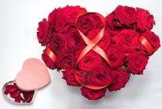 O coração fez a rosas vermelhas o ramalhete que a figura de fita vermelha 8 caixa da forma do coração com pétalas isolou o fundo  Imagem de Stock