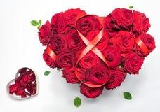 O coração fez a rosas vermelhas o ramalhete que a figura de fita vermelha 8 caixa da forma do coração com pétalas isolou o fundo  Imagens de Stock
