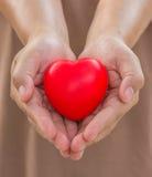 O coração nas mãos para dá com amor imagens de stock