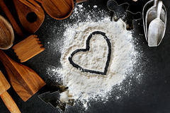 O coração tirado na farinha do cozimento com cozimento fornece a beira Foto de Stock Royalty Free