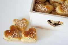 O coração três salgado deu forma a cookies e à caixa de madeira decorativa completamente dele na tabela branca imagem de stock