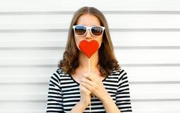 O coração vermelho de beijo da mulher do close-up do retrato deu forma ao pirulito ou esconde seus bordos na parede branca imagem de stock