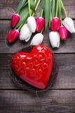 O coração vermelho decorativo no ninho e em tulipas brilhantes da mola floresce Foto de Stock Royalty Free