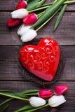 O coração vermelho decorativo no ninho e em tulipas brilhantes da mola floresce Fotografia de Stock