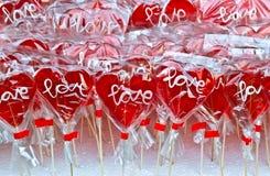 O coração vermelho deu forma ao pirulito em um suporte do mercado foto de stock