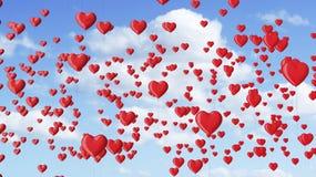 O coração vermelho deu forma a balões no céu azul com nuvens Fotos de Stock Royalty Free