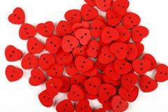 O coração vermelho deu forma a costurar botões sobre o branco foto de stock