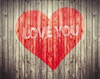 O coração vermelho e ama-o frase no fundo de madeira Símbolo romântico pintado imagem de stock royalty free
