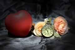 O coração vermelho e aumentou com o relógio de bolso do ouro do vintage no fundo preto da tela Amor do conceito do tempo Ainda es Foto de Stock