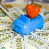 O coração vermelho em um cabriolet azul contra o contexto de muitas contas de cem-dólar espalhou para fora em um círculo Dia do ` Imagens de Stock Royalty Free