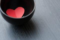 O coração vermelho está em uma bacia no fundo de madeira cinzento imagem de stock