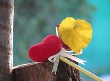 O coração vermelho feito de uma toalha, da vara com o lápis, da fita do laço e do coração deu forma às folhas amarelas em um vidr imagens de stock royalty free
