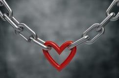 O coração vermelho guardou por um fundo chain de aço Fotografia de Stock Royalty Free