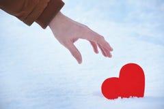 O coração vermelho perdido está sozinho em um dia de Valentim, coração em uma neve fria do inverno, com uma luz de brilho ao redo fotos de stock