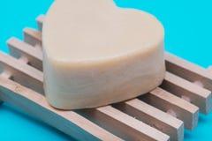 O cora??o deu forma ao sab?o do leite da cabra no prato de madeira natural separado no azul fotografia de stock royalty free