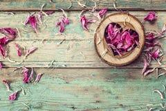 O coração cinzelou na madeira com as pétalas cor-de-rosa da peônia no pa velho do grunge Imagens de Stock Royalty Free