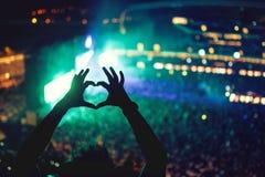 O coração deu forma às mãos no concerto, amando o artista e o festival Concerto da música com luzes e silhueta de um homem que ap Fotografia de Stock Royalty Free