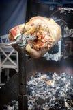 O cordeiro é fritado em um cuspe sobre carvões quentes imagem de stock