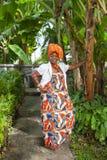 O corpo completo vertical de uma mulher afro-americano alegre poses nacionais coloridas brilhantes vestindo de um vestido foto de stock royalty free