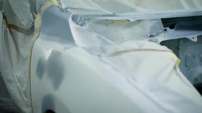 O corpo de carro sem capa e rodas, é preparado pintando em uma loja de reparação de automóveis, estando em uma garagem filme