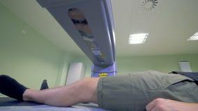 O corpo inferior de um paciente masculino está obtendo analisou por uma máquina de raio X filme
