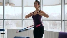 O corpo saudável, fêmea magro executa o exercício com o anel plástico contra de grandes janelas filme