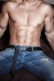 O corpo 'sexy' do homem senta-se na cama Imagens de Stock