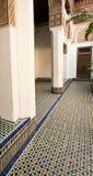 O corredor com mosaico telhou o assoalho que conduz a uma porta de madeira em um palácio marroquino Fotografia de Stock Royalty Free