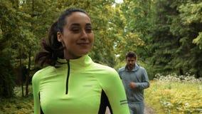 O corredor da mulher olha de volta a seu sócio ao correr e ao ganhar a raça no parque video estoque
